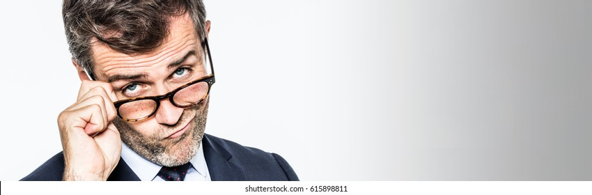 pouting far-sighted elegant businessman moving his eyeglasses down for management disappointment, disapproving, copy space, white background studio