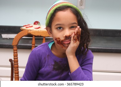 pouting girl with a messy face of chocolate