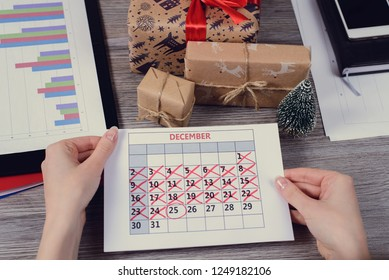 Pov above first person high angle above overhead close up view photo of hands holding calendar with crossed numbers days over wooden table