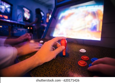 POV angle on hands playing vintage arcade game with an opponent, in a dark shade room full of arcade games and pinballs