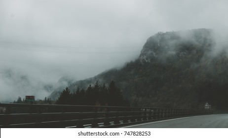 POV car driving on a mountain highway, clouds flying low