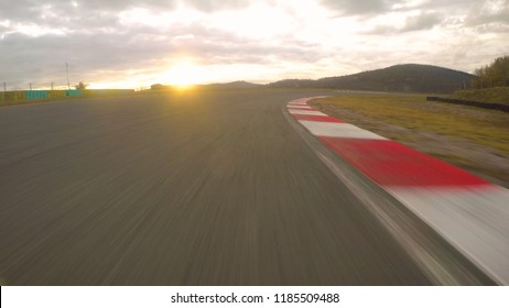 POV: Cinematic view of driving a fast car down an empty raceway at beautiful sunrise. Gentle golden sun rays shine on asphalt racetrack from behind the horizon during an adrenaline filled track day.