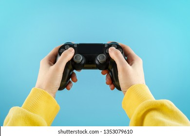 POV close up and cropped photo of cool girl in trendy and stylish yellow hoodie. She holding in hands black button joystick and standing against light blue background in studio