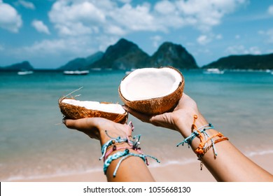 POV: coconut in girl hands on the tropical beach over sea landscape. Travelling tour in Asia: El Nido, Palawan, Philippines.