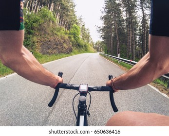 POV Cycling. Young adult man climbing a mountain road with a racing bicycle on a spring afternoon. Personal perspective