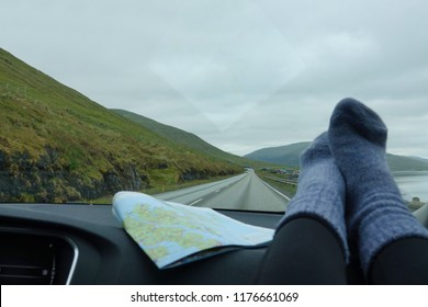 POV: Driving down scenic coastal road with your feet resting on the dashboard in cozy woolen socks. Cool shot of unrecognizable woman's legs on the car dashboard as she drives down the empty road.