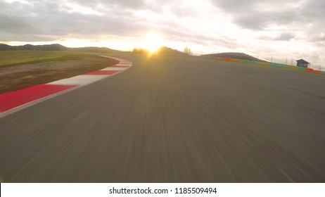 POV: Driving a fast car along the scenic asphalt racetrack on a cloudy evening. Breathtaking first person view of racing a supercar through the long turns of a modern circuit. Adrenaline joyride.