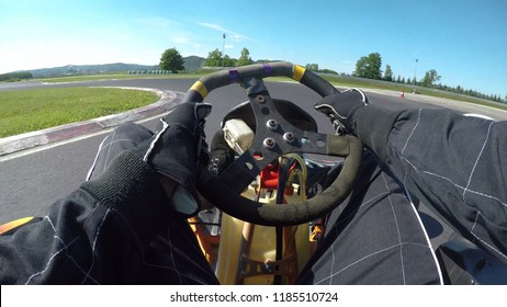 POV: Driving a fast go-kart in a black suit through sharp bends of a bumpy asphalt racetrack. Cinematic first person view of steering a go cart while racing in a fun competition on the sunny circuit.