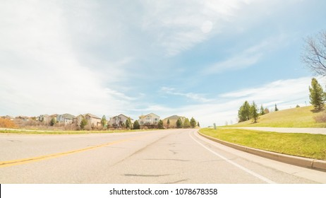 POV- Driving on paved road in suburban neighborhood in Colorado.