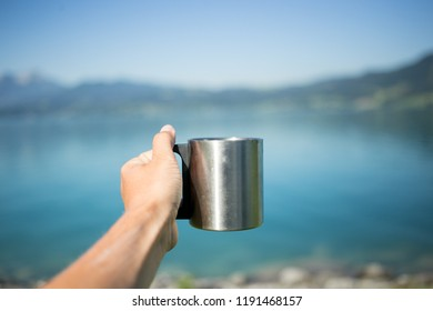 POV of female tourist or traveller hold metal camping mug out in hand with mountain lake or sea in background, enjoys amazing views and real outdoor nomad lifestyle, drinks natural coffee or tea