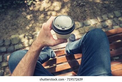 POV image of man sits on a bench and holding paper cup of coffee at a summer day in the park