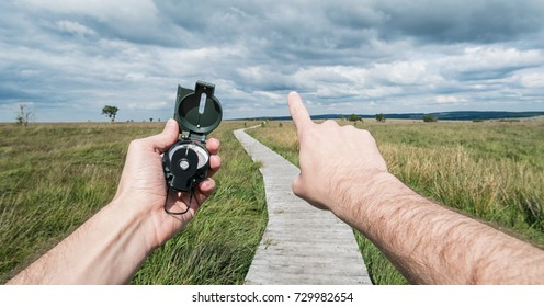 POV image of traveler man holding a compass and pointing direction in the landscape.