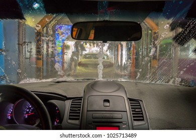 POV interior car in car wash with suds on front windshield
