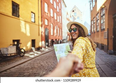 POV of a laughing young woman wearing sunglasses and reading a map while leading another person by the hand through cobblestone city streets