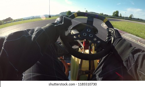 POV, LENS FLARE: Having fun racing a go kart along a bumpy asphalt racetrack on a sunny day. Cool shot of arms and legs driving a fast go-cart around the raceway during a cool time trial competition.