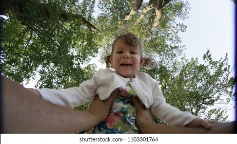 POV: Lifting a cute little toddler girl with adorable pigtails high in air in a sunny park. Cheerful baby daughter laughing while her daddy holds her high up in the sky. Energetic child having fun.