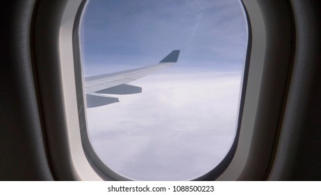 POV: Looking through a small window at the endless clouds and large metal wing of a modern airplane. Awesome view of the vast space and thick clouds from a window seat of a transatlantic jet plane.