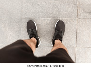 POV. Male runner looking down at his feet, wearing sports shoes footwear, ready for jogging