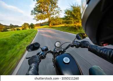 POV of motorbiker holding steering bar, riding in beautiful sunset light. Travel and freedom, outdoor activities