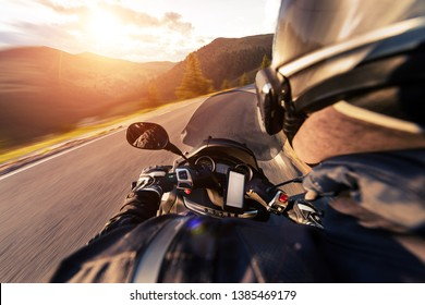 POV of motorcycle driver riding on Alpine road. Outdoor photography. Travel and sport, speed and freedom concept