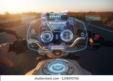 POV of a motorcyclist driving on a road at sunset, his futuristic motorcycle on which the holographic graphics appear. Concept of: travel, transport, road, freedom and relaxation.