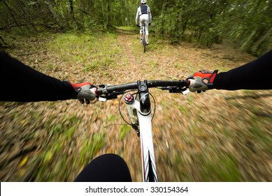 POV, Original point of view. Couple of cyclist during a mountain bike race in the forest.