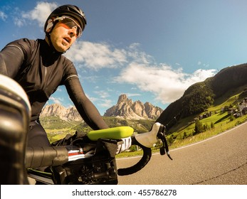 POV, Original point of view. Young man on bicycle take a selfie. Training on road bike on a mountainous road in a Dolomites.