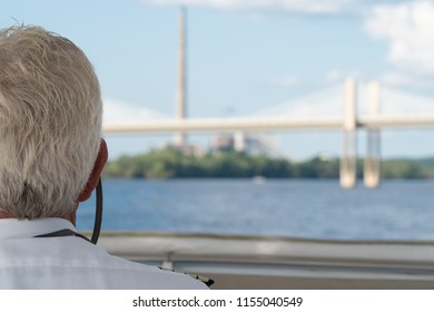 POV over the shoulder view of boat captain sailing down a river towards highway bridge overpass during day time. Navigation to check water depth for nautical safety