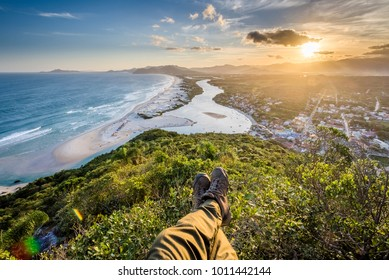 POV photo of my feet and legs with hiking shoes with a view during sunset time from Pedra do Urubu Hill to Guarda do Embau Beach and Madre River, Santa Catarina State, South Brazil