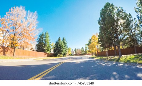 POV point of view - Driving through typical suburban residential neighborhood in Autumn.