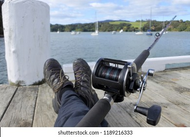 POV (point of view) of a man fishing with a fishing rod from a boat jetty.