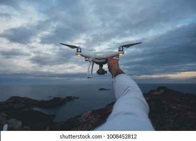 POV shot of drone pilot or professional stock or nature photographer holding futuristic drone up in air in front of stormy skies, ready to fly technology into air and shoot aerial photos and videos