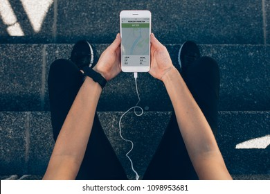 POV shot of female athlete checking mobile phone after running workout outdoors. Woman using fitness app for summary of the run.
