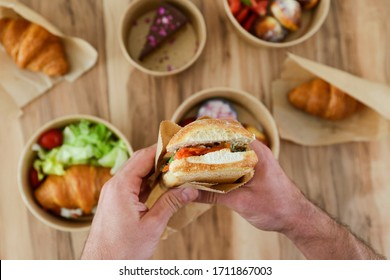 Pov shot of man holding italian panini sandwich over the wooden table with takeout food. French croissant with salmon and chocolate cheesecake. Close up, top view, pov, copy space, background.