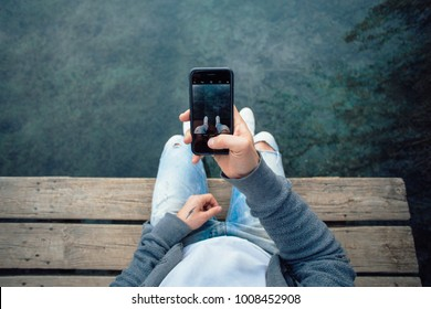 POV shot of man making photo of his sneakers hanging over water on smartphone , to share on social media or internet website, mobile photography for amateurs