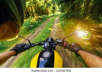 POV shot of man riding on a motorcycle in the forest. copyspace for your individual text.