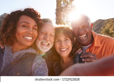 POV-Schuss von Senioren, die für Selfie beim Wandern auf dem Weg in die Landschaft zusammen pochen