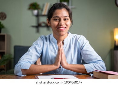POV shot of young business woman doing namaste gesture to camera - Concept of video chat, conference or vlogging from home by looking at camera