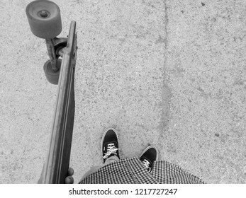 POV shot of a young man holding a longboard in his left hand staring at the concrete ground and standing still. He is dressed with a squared black and white shirt, beige chinos and black sneakers.