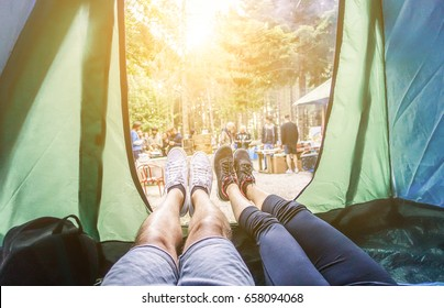 Pov view of happy couple inside tent at camping wood festival - Young people having fun on summer vacation into the wood - Travel,love,nature concept - Main focus on left feet - Warm contrast filter