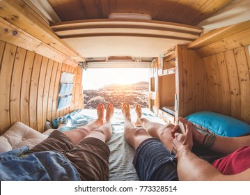 Pov view of happy couple inside minivan at sunset - Young people having fun on summer vacation - Travel,love and nature concept - Focus on feet - Warm contrast filter