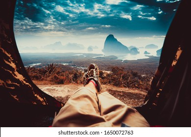 POV view of hipster tourist inside tent on front of mountains and sea. Adventure travel lifestyle wanderlust