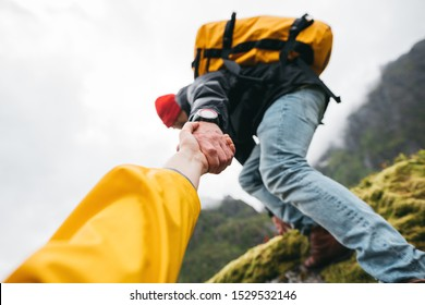 POV view on brave tourist helping his active friend holding to hand climbing to rock. Two travelers climb to mountains lifestyle outdoor vacation