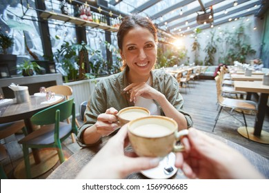 POV view of smiling woman holding coffee cup talking to friend across table in cafe