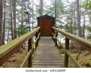 A PoV view of someone walking towards a remote wooden outhouse in the forest in the gulf islands of british columbia, canada.
