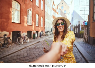 POV of a young woman holding a map and laughing while leading a person by the hand through city streets