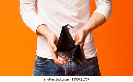 Poverty and absence of money. Empty wallet in hands of unemployed black man, orange studio background