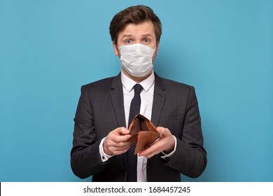 Poverty and absence of money. Unemployed sad caucasian man in medical mask and suit showing empty wallet, blue studio background