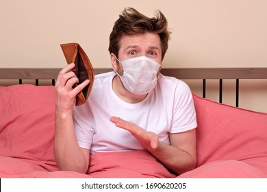 Poverty and absence of money. Unemployed sad caucasian man in medical mask sitting at home on quarantine or isolation because of covid showing empty wallet. He has no money for living.