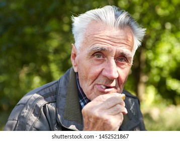 Poverty and bread. Elderly poor man eating bread